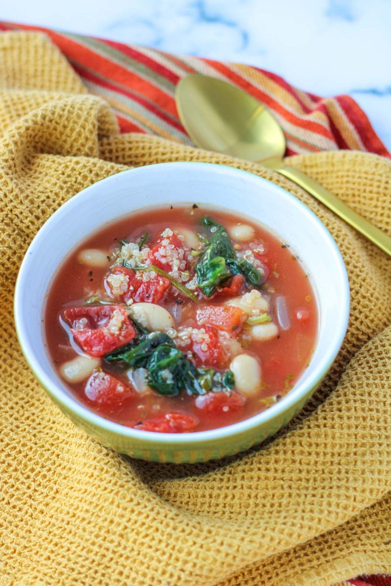 Easy Winter Soup with Beans in a white bowl with a gold spoon