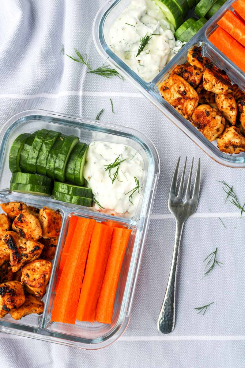 Glass bento box style containers with cucumbers, carrots and chicken with greek dip