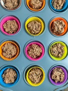 A muffin tin pan with silicone baking cups filled with gluten-free chocolate muffins with quinoa flakes ready for the oven