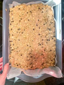 A large baking pan filled with Gluten-Free Oatmeal Breakfast Bars with Chocolate ready for oven