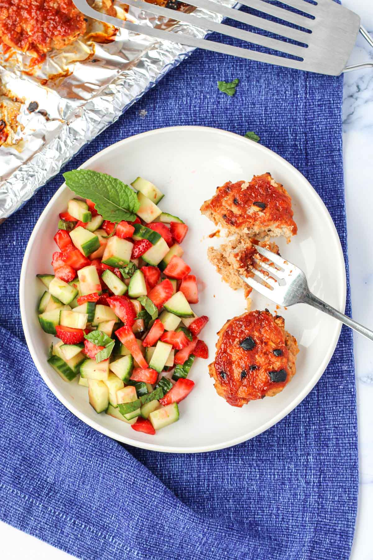Gluten-Free Turkey Burgers on a white plate with strawberry cucumber salad