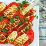 Grilled Halloumi Salad with Tomato and Parsley on a white plate with silver cutlery
