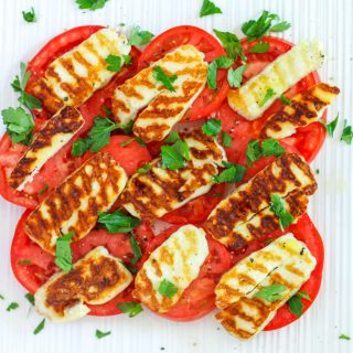 Grilled Halloumi Salad with Tomato and Parsley on a white platter