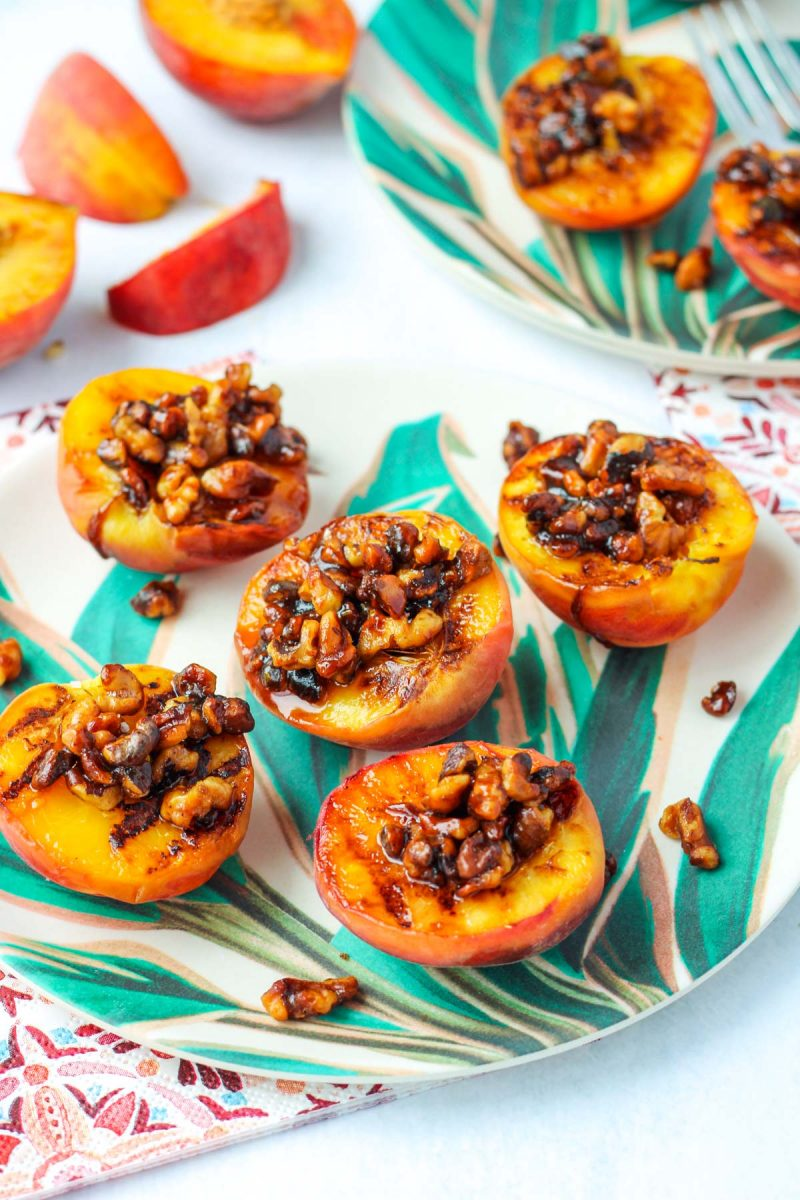 Grilled Peaches with Walnuts on a plate with tropical leaves