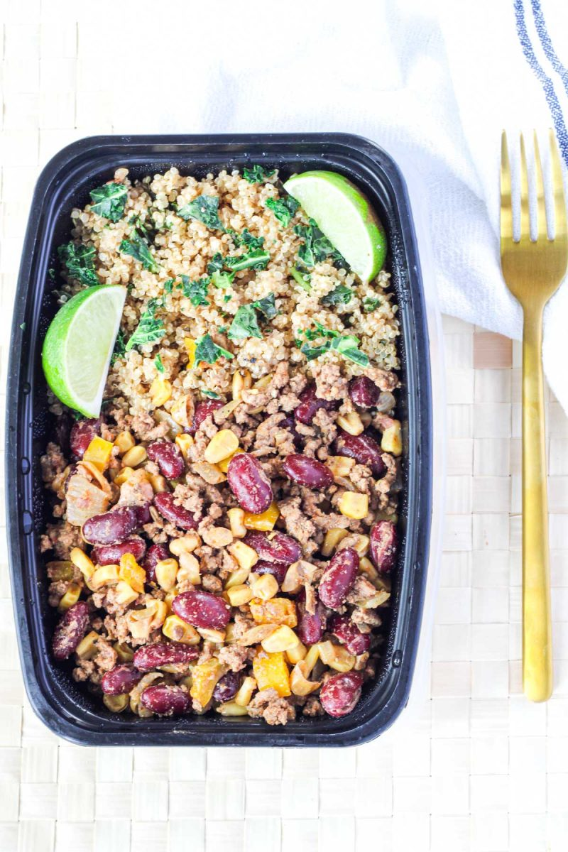 A black food prep container filled with beef and corn mixture with quinoa and lime wedges