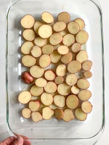 Large glass baking dish covered in sliced potatoes