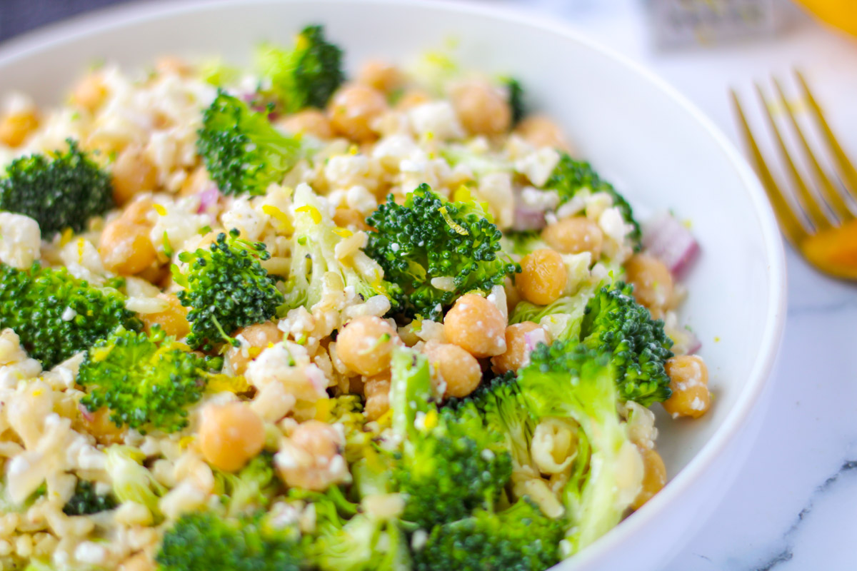 Lemony Brown Rice, Broccoli and Feta Salad in a white dish with a gold fork beside