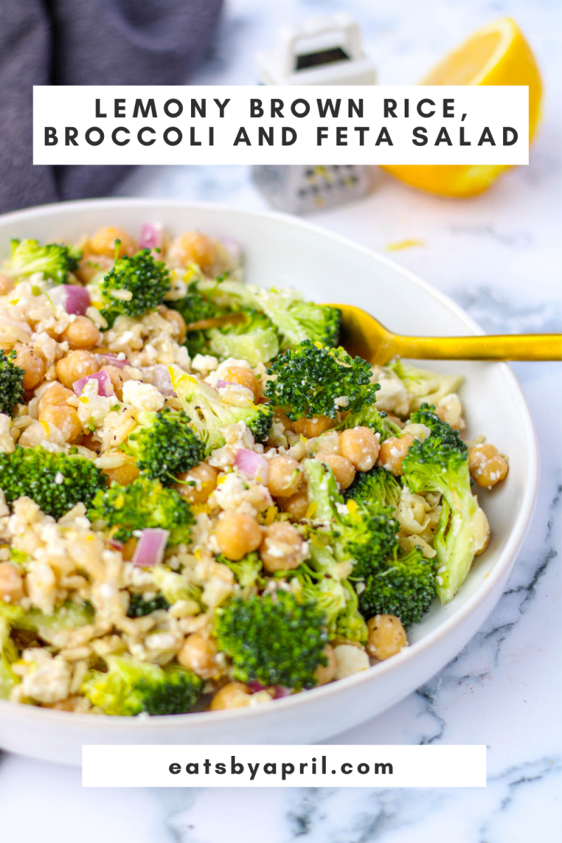 A dish of chopped broccoli, chickpeas and rice on a white dish with a gold fork
