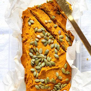 a loaf of pumpkin bread topped with pepitas with a gold knife beside
