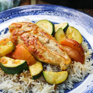 One Pan Chicken Breast with Zucchini and Peaches on a blue and white plate