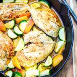 One Pan Chicken Breast with Zucchini and Peaches in a castiron skillet on a brown cutting board