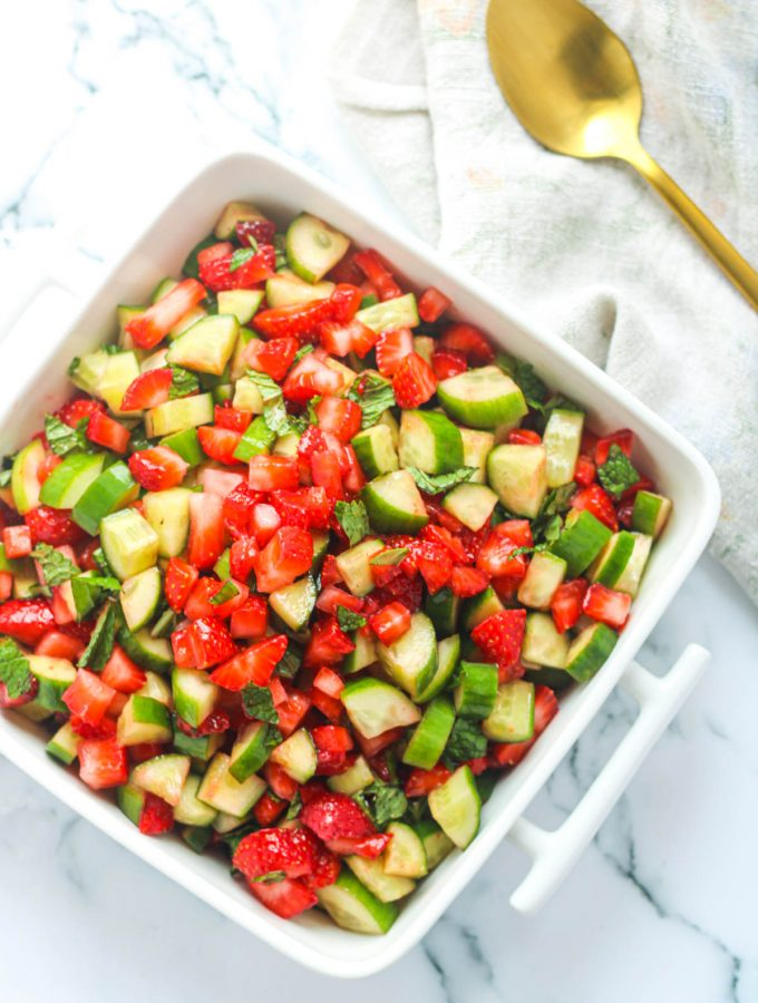 Overhead shot of Strawberry Cucumber Salad with Mint in a white serving dish on a white marble countertop