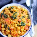 Overhead shot of a chickpea curry with Spinach in a blue bowl
