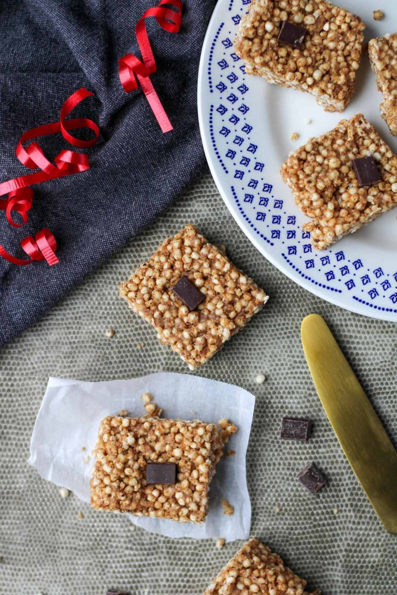 Puffed Quinoa Bars with Almond Butter on a grey placemat with a gold knife