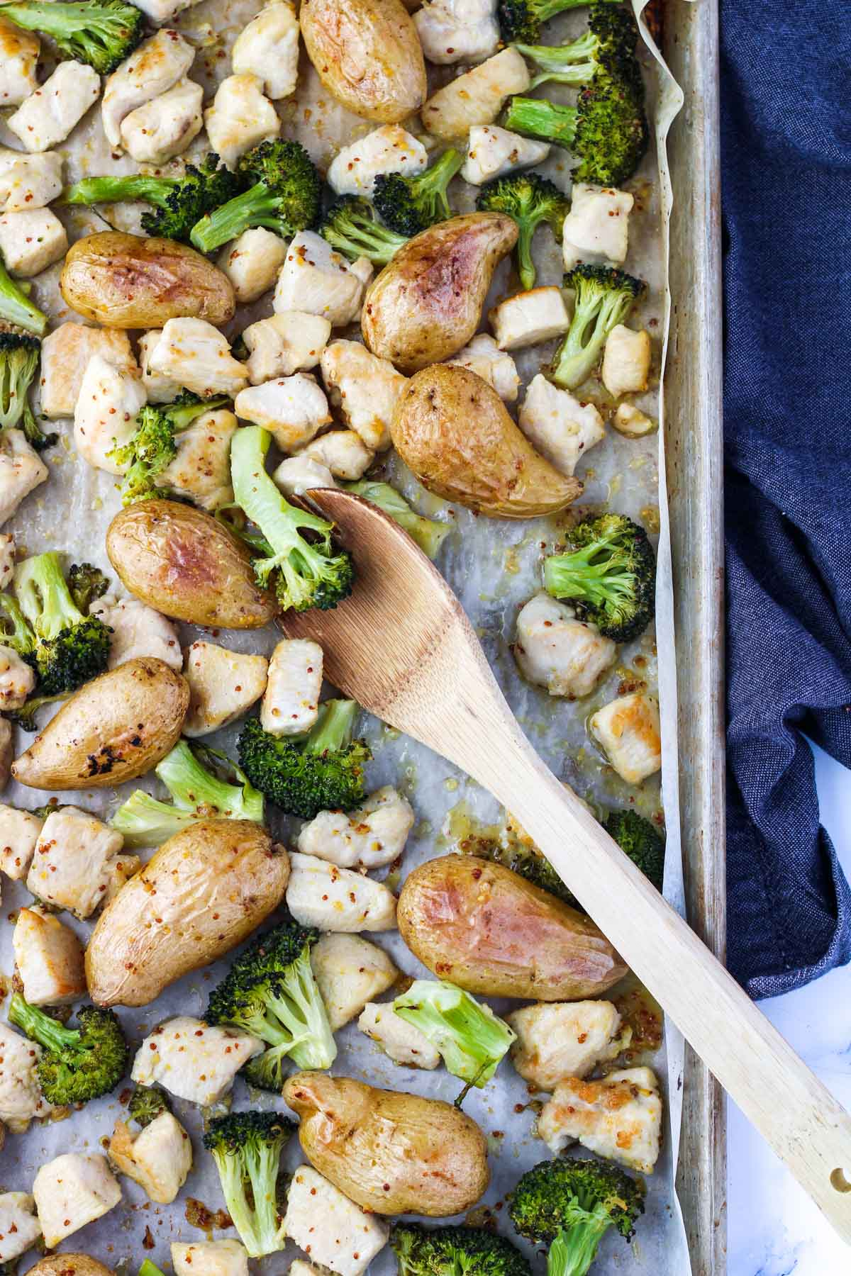 Sheet Pan with broccoli, chicken and potatoes with a wooden spoon in it