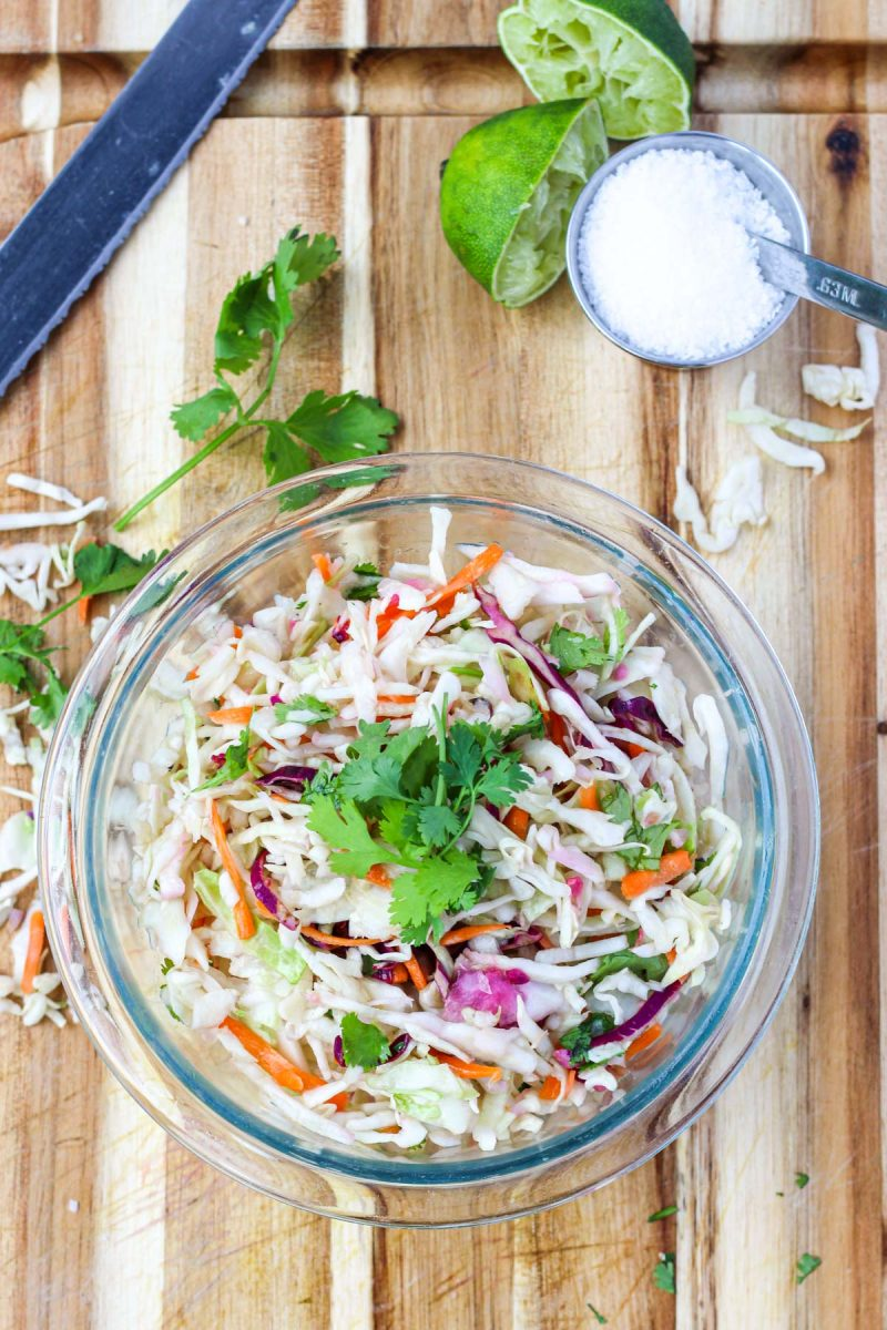 Clear bowl filled with coleslaw on a cutting board