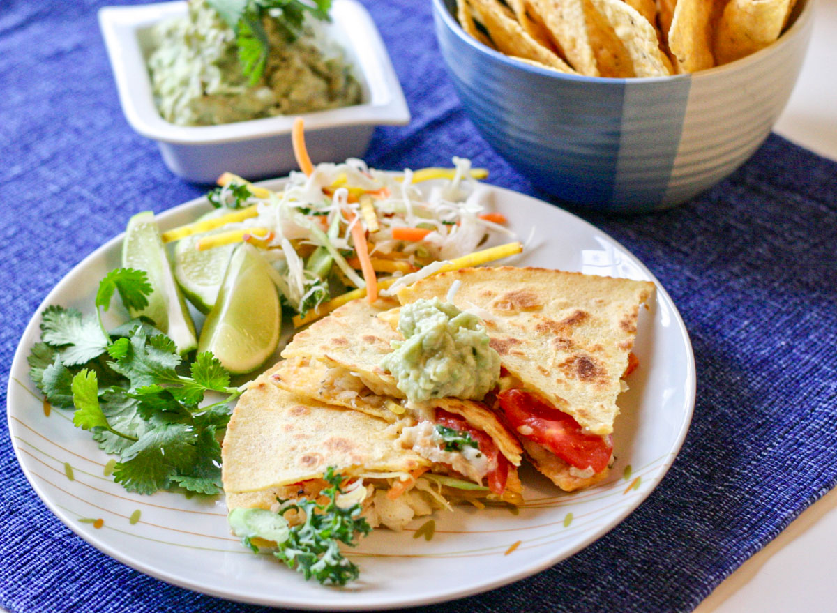 Simple Haddock Quesadillas on a blue placemat and a white plate with a bowl of tortiall chips in the background