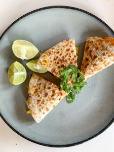 Simple Haddock Quesadillas on a blue plate with cilantro and lime wedges
