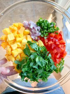 Simple Mango Salsa ingredients in a clear class bowl