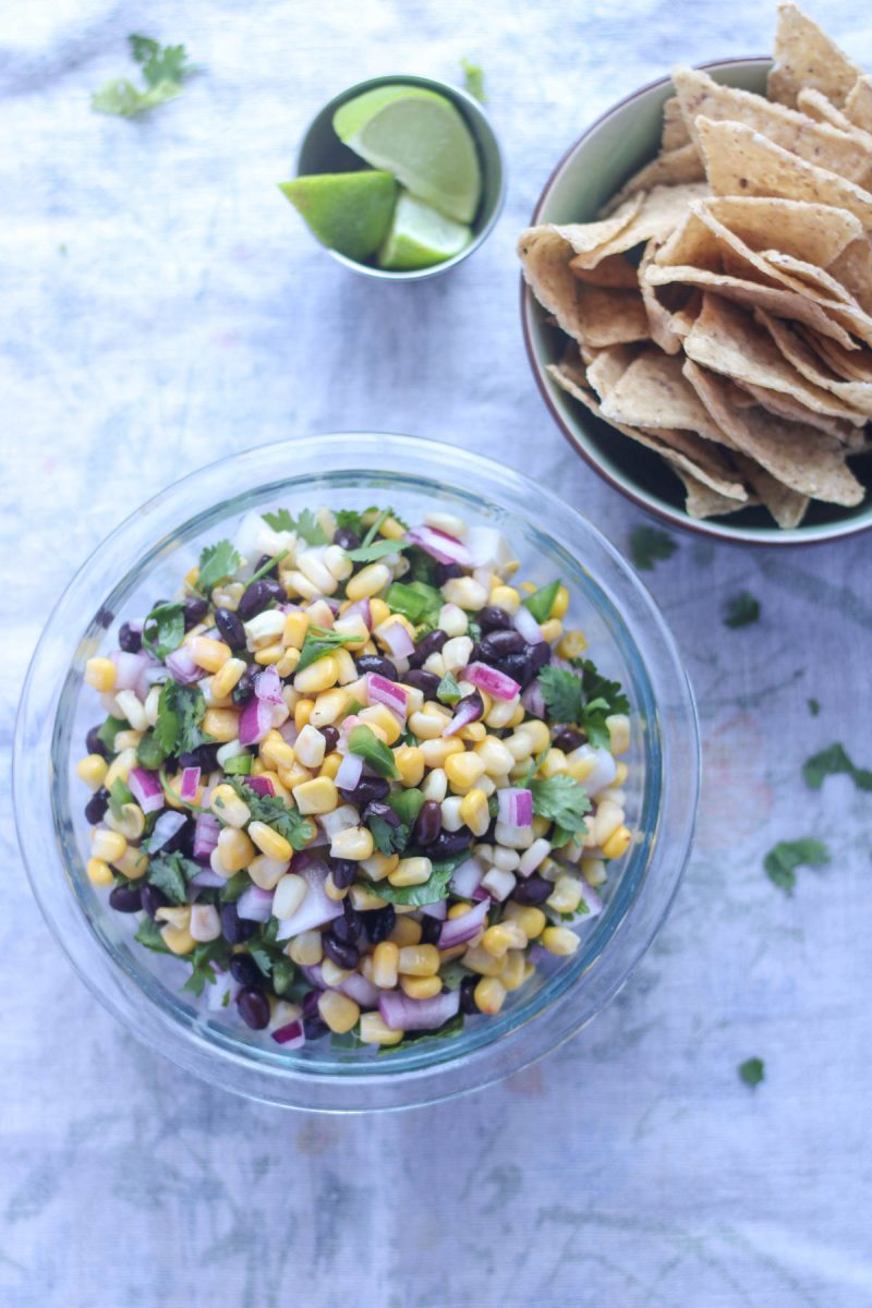 Summer Corn and Black Bean Salsa in a clear glass bowl with a bowl of chips and lime wedges on the side