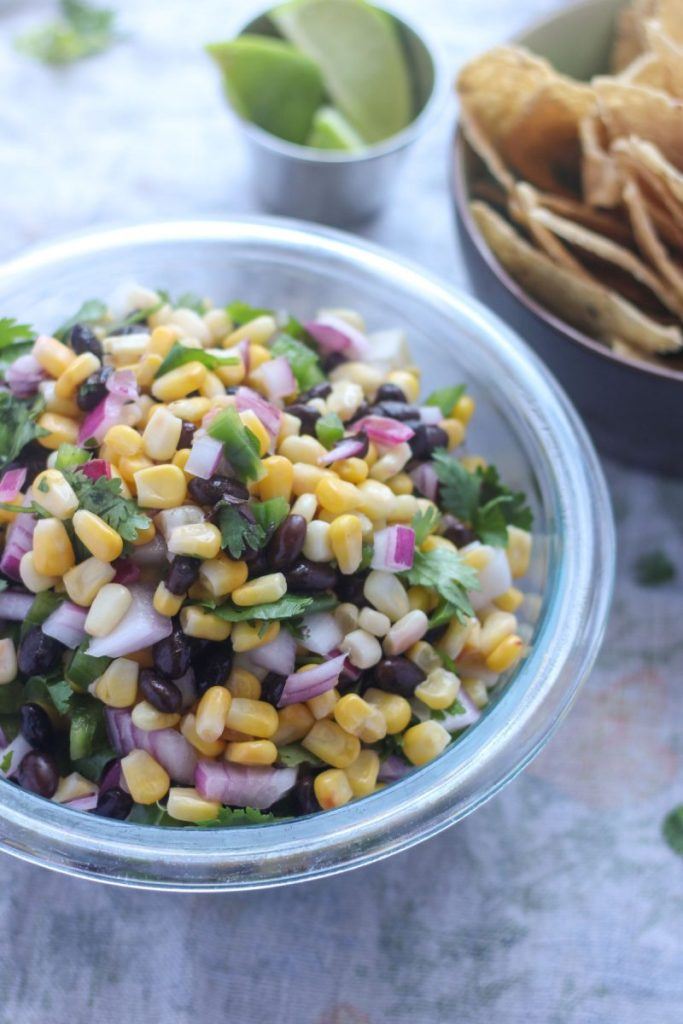 A bowl of corn salsa with a small bowl of chips beside it.