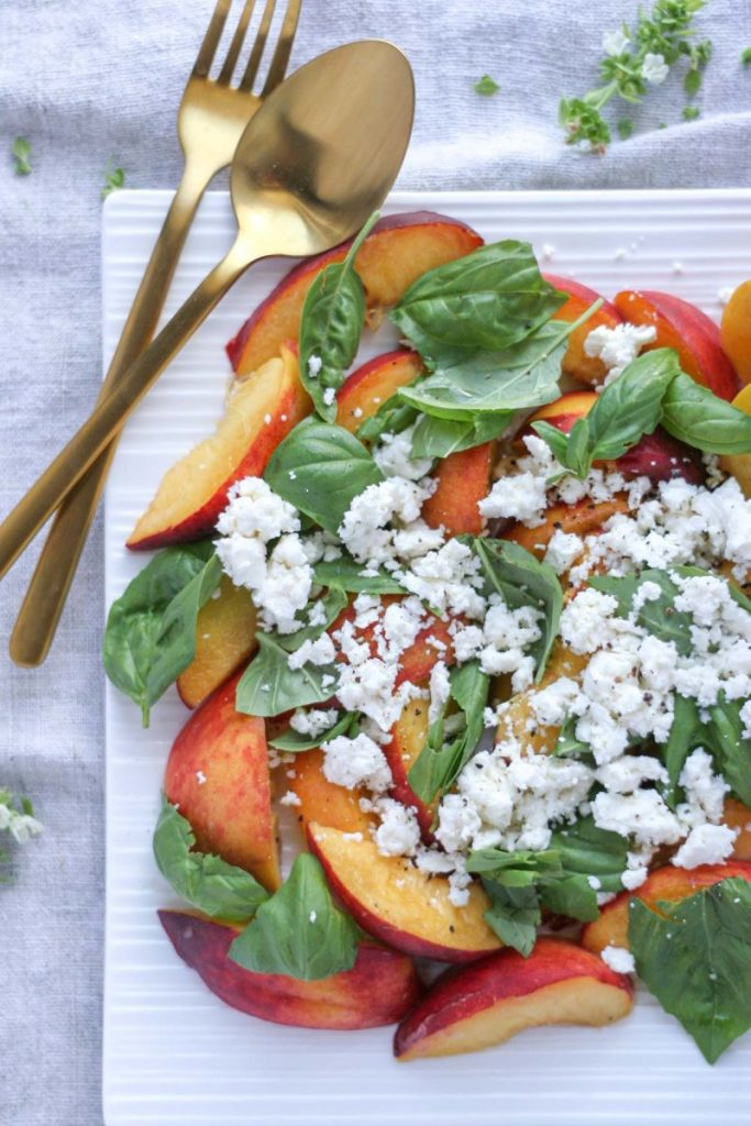 Summer Peach Basil Salad with Feta on a white platter with gold flat wear