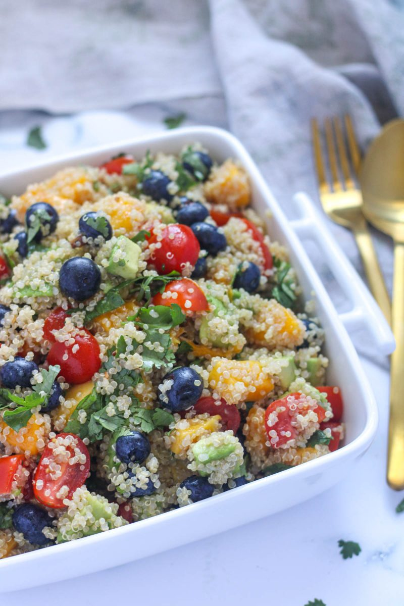 Summer Quinoa Salad with Mango and Blueberries in a square white dish with a gold fork and spoon beside it