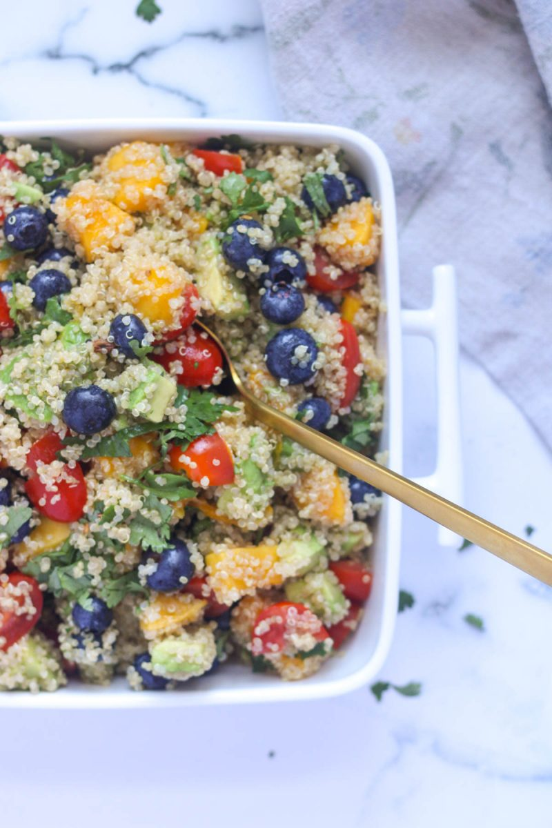 Summer Quinoa Salad with Mango and Blueberries ina white dish with a gold spoon in it