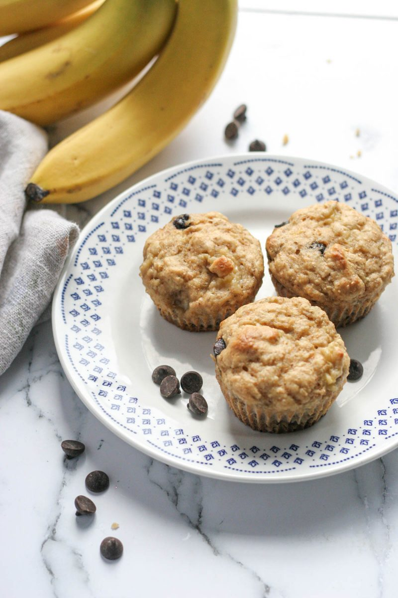 Three Best Ever Banana Chocolate Chip Muffins on a white plate with chocolate chips and bananas in the background
