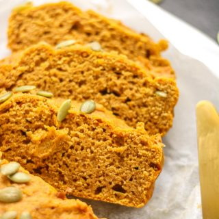 Three slices of pumpkin loaf topped with pumpkin seeds on parchment paper