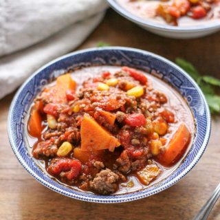 Two blue bowls filled with Easy Weeknight Hamburger Soup with Sweet Potatoes on a brown wood table