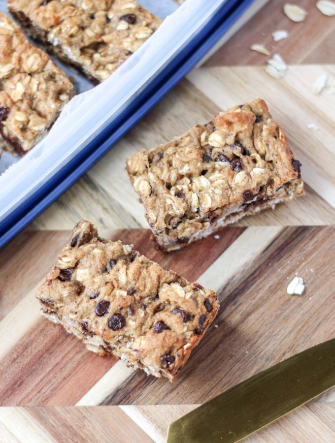 Two square of gluten-Free Oatmeal Breakfast Bars with Chocolate on a wood cutting board