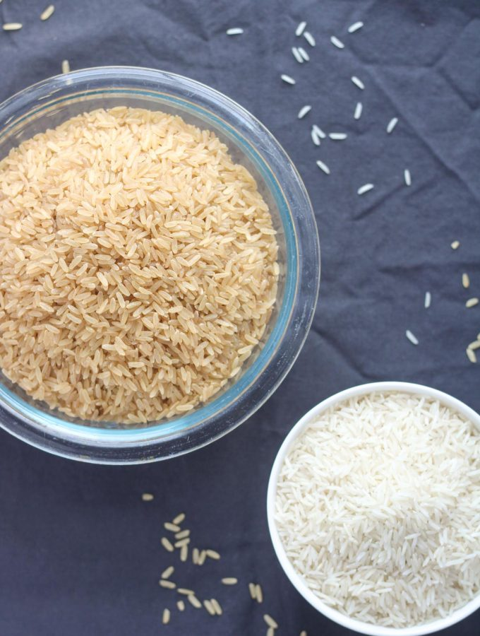 a large bowl of brown rice and a small bowl of white rice
