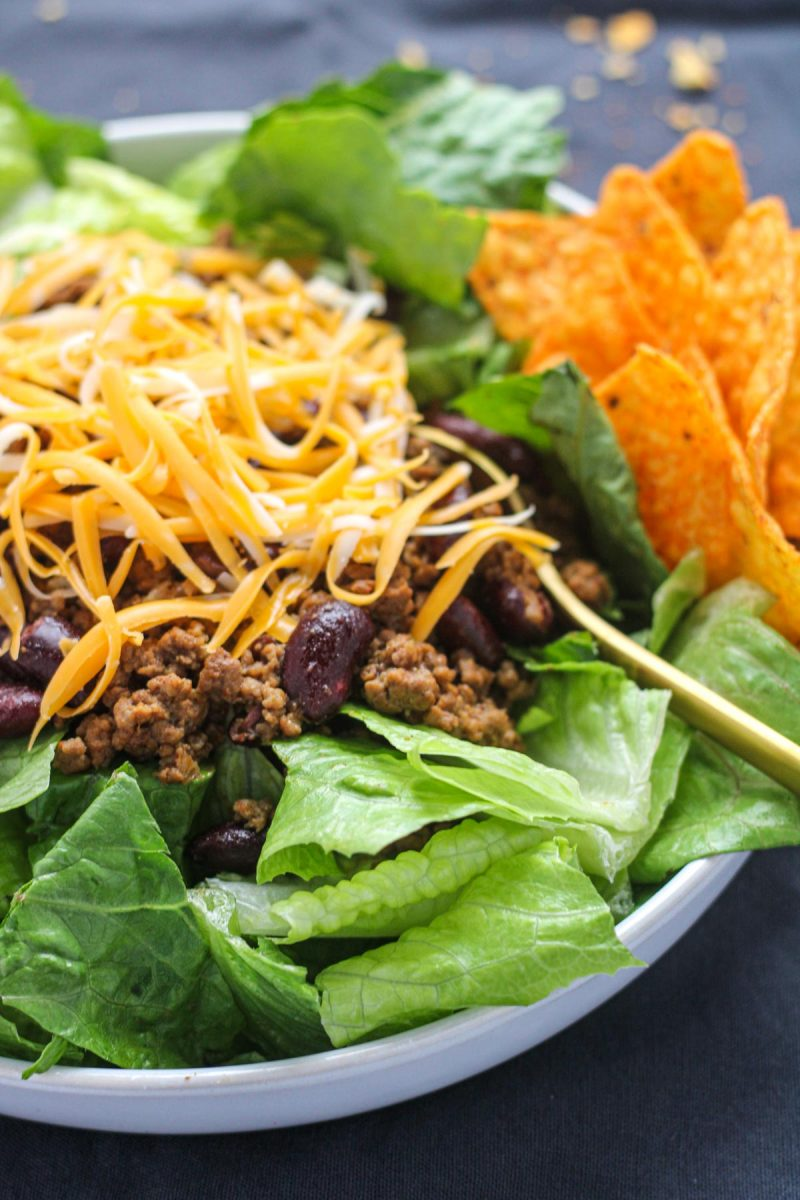 White plate with romaine lettuce ground beef and shredded cheese with nacho chips