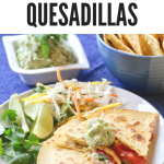 Simple Haddock Quesadillas on a white plate with lime wedges and cilantro on the side